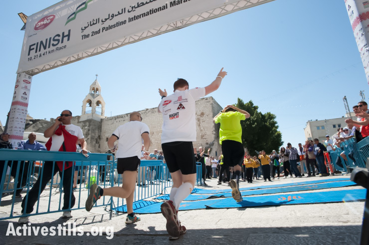 Runners in the second annual Palestine Marathon cross the finish line near the Church of the Nativity in Bethlehem's Manger Square, West Bank, April 11, 2014. (photo: Activestills.org)