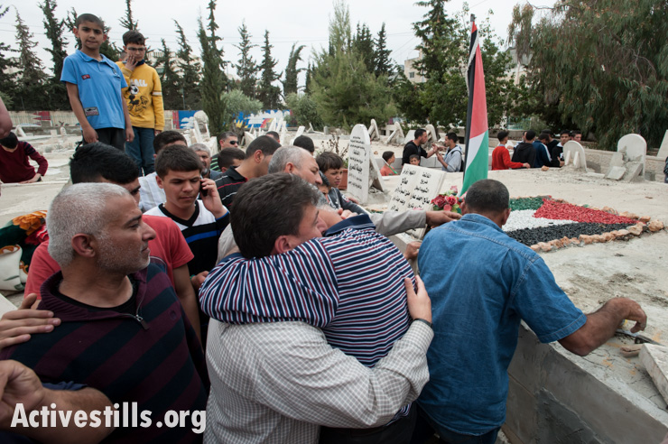 A supporter embraces Hasan Katamish (left) after the burial of his sister Noha in the cemetery in Aida Refugee Camp, West Bank, April 15, 2014. Noha Katamish, who had asthma, died from the effects of a tear gas grenade fired into her home by Israeli forces the previous day. She was the mother of one daughter.