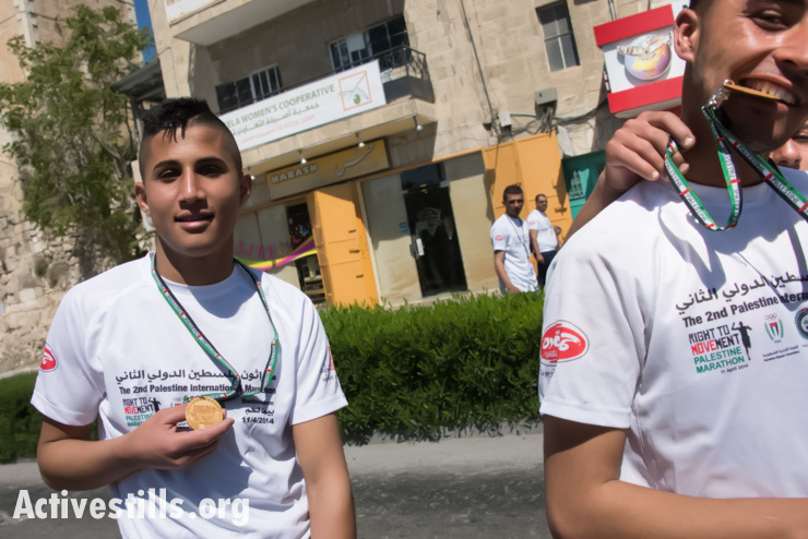 Palestinian youth show off their olivewood participants' medals following the second annual Palestine Marathon in the West Bank town of Bethlehem, April 11, 2014. (photo: Activestills.org)