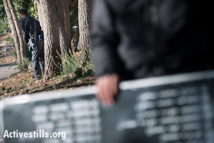 An Israeli policeman who had been escorting the march urinates within sight of the panels bearing the names of those killed in the Deir Yassin massacre as the commemoration concludes near the grounds of the Kfar Shaul mental hospital. (photo: Activestills.org)