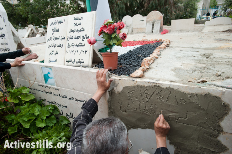 A family member makes a temporary inscription at the tomb of Noha Katamish until a finished grave marker can be placed in the cemetery of Aida Refugee Camp, West Bank, April 15, 2014. Noha Katamish, who had asthma, died from the effects of a tear gas grenade fired into her home by Israeli forces the previous day. She was the mother of one daughter. She was buried next to the grave of Salih Amarin, who was 15 when he was shot in the head and killed by Israeli forces in Aida Refugee Camp in January 2013.