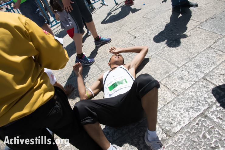 A runner in the second annual Palestine Marathon collapses in exhaustion after crossing the finish line in Bethlehem's Manger Square, West Bank, April 11, 2014. (photo: Activestills.org)