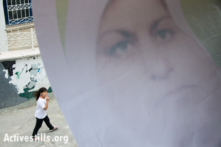A girl passes a banner bearing an image of Noha Katamish to honor her memory in Aida Refugee Camp, West Bank, April 15, 2014. Noha Katamish, who had asthma, died from the effects of a tear gas grenade fired into her home by Israeli forces the previous day. She was the mother of one daughter.