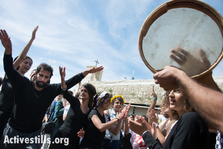 On Easter Monday in the displaced Palestinian village of Iqrit, youth dance and make music in front of the town's church. Northern Israel, April 21, 2014. Iqrit's original inhabitants were forcibly evacuated in the Nakba of 1948. Though the Israeli high court granted the residents, who are Palestinian citizens of Israel, the right to return to their homes in 1951, the military destroyed the village and has since prevented their return. Only the village's church and cemetery remained intact, and are still used by village residents while they campaign for a full return.