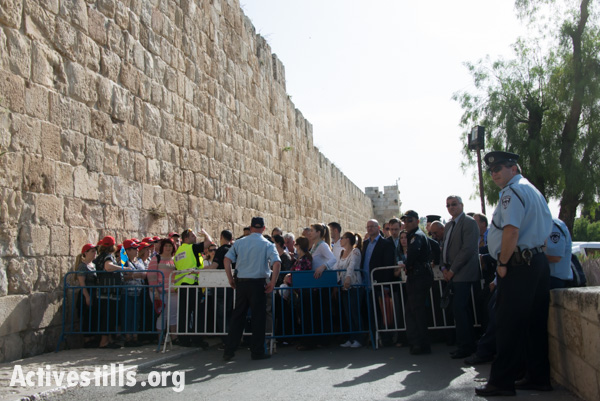 "An Israeli police checkpoint blocks access to the Old City of Jerusalem, April 19, 2014. The day before Easter, thousands of Palestinian Christians and international pilgrims attempt to enter Jerusalem's Old CIty to participate in the ""Saturday of Light"" or ""Holy Fire"" celebration in the Church of the Holy Sepulcher, the traditional site of the crucifixion, burial and resurrection of Jesus. (photo: Ryan Rodrick Beiler/Activestills.org)"