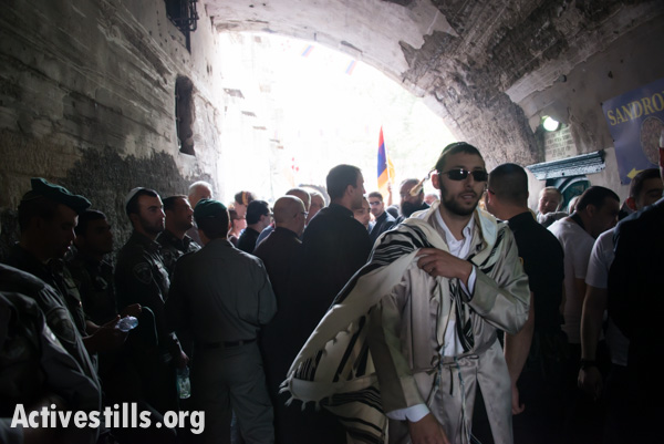 Israeli police restrict the movement of Christians in the Armenian Quarter of the Old City of Jerusalem while letting a Jewish man pass through, April 19, 2014. (photo: Ryan Rodrick Beiler/Activestills.org)