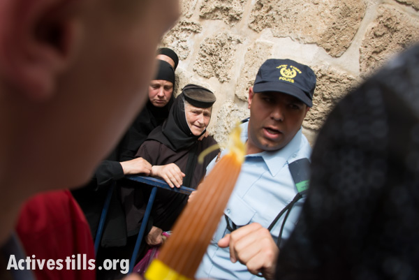 Orthodox Christian nuns stand trapped behind an Israeli police barrier in the Old City of Jerusalem, April 19, 2014. (photo: Ryan Rodrick Beiler/Activestills.org)