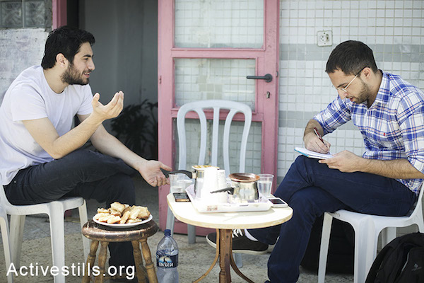 Majd Kayyal (left) sits on the terrace of his Haifa home, discussing what he describes as his unforgettable trip to Beirut, and his detention upon returning to Israel, with Rami Younis (Photo by Shiraz Grinbaum/Activestills.org)