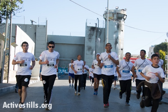Runners take part in the annual Palestine Marathon in Bethlehem under the shadow of a new weapon (top left) perched atop the separation wall. (photo: Activestills)