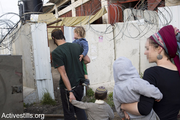 """A Jewish settler family moves into the """"House of Contention"""" settlement in the West Bank city of Hebron, April 13, 2014. Three Israeli settler families moved into a contested home in Hebron, following a years-long legal battle and culminating on Sunday with the authorization of Israeli Defense Minister Moshe Ya'alon. The new building signifies the first new settlement in Hebron since the 1980s. (photo: Activestills.org)"""