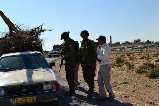 Soldiers set up roadblocks and detain vehicles in South Hebron Hills, West Bank. 22 April, 2014 (Photo: Dahlia Scheindlin)