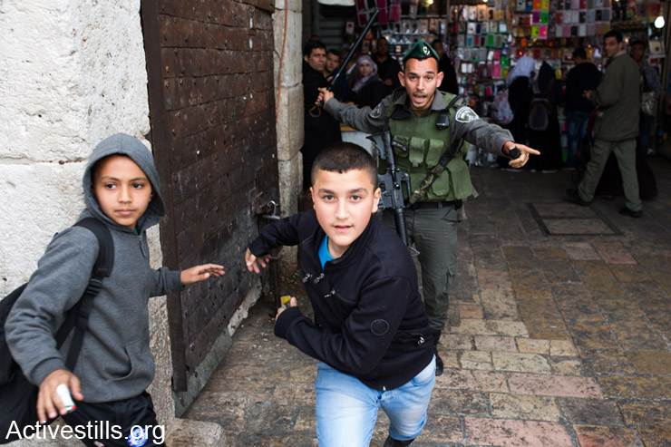 An Israeli border police officer chases Palestinian children during a Land Day demonstration in Damascus Gate, East Jerusalem on March 30, 2014. Land Day is held on the anniversary of March 30, 1976, when Palestinian villages and cities across the country witnessed mass demonstrations against the state's plans to expropriate 2,000 hectares of land in the Galilee region. In coordination with the military, some 4,000 police officers were dispatched to quell the unrest. At the end of the day, six Palestinian citizens of Israel were killed by state forces. (photo: Activestills.org)