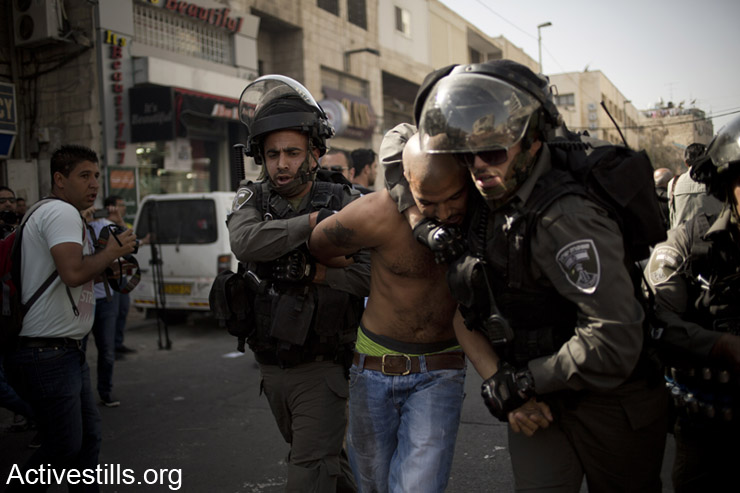 A Palestinian man is arrested by Israeli border police during a demonstration marking Land Day near the Old City in East Jerusalem on March 29, 2014. Land Day is held every year to mark the deaths of six Palestinians protesters at the hands of Israeli police and troops during mass demonstrations on March 30, 1976, against plans to confiscate Arab land in Galilee. (photo: Activestills.org)