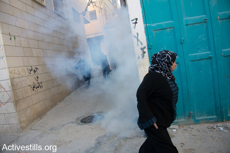 A Palestinian woman flees from tear gas launched by Israeli forces inside Aida Refugee Camp, Bethlehem, West Bank, March 28, 2014. (photo: Activestills.org)