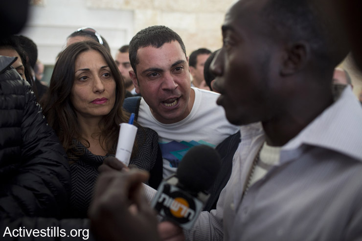 Residents of south Tel Aviv argue with an African asylum seeker during the the High Court of Justice hearing regarding a petition by human rights NGOs against the Infiltration Law, West Jerusalem, April 1, 2014. (photo: Activestills.org)