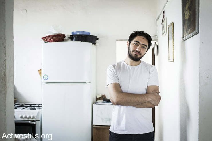 Majd Kayyal, a Palestinian researcher and journalist, poses for a portrait in his home, Haifa, April 19, 2014. Israeli security services arrested Kayyal last week at the Sheikh Hussein crossing at the Israeli-Jordanian border, after he returned from a visit in Lebanon. Kayyal attended a conference that marked the 40th anniversary of the As-Safir newspaper in Beirut. He was released after five days of interrogation after massive public pressure. (Activestills.org)