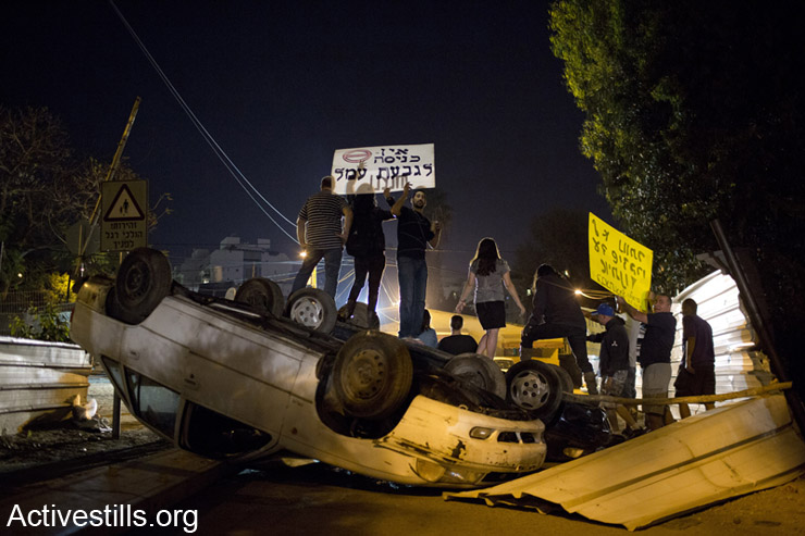 Local residents and activists holds signs near a barricade they set with from cars to prevent a planed eviction of houses in the Gival Amal neighborhood in Tel Aviv, April 22, 2014. The main road leading to the neighborhood was blocked after six houses received eviction orders, starting April 23 due until May 12th, 2014. According to the plan, 130 families living in the area since 1948, will be evicted without proper compensation. (Activestills.org)