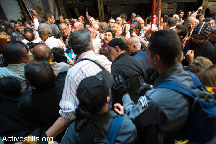"""Israeli police push worshipers in the Church of the Holy Sepulchre in the Old City of Jerusalem, April 19, 2014. The day before Easter, thousands of Palestinian Christians and international pilgrims attempt to enter Jerusalem's Old City to participate in the """"Saturday of Light"""" or """"Holy Fire"""" celebration in the Church of the Holy Sepulchre, the traditional site of the crucifixion, burial and resurrection of Jesus. The Israeli High Court of Justice ruled this month that Palestinians rights are being violated by checkpoints and other restrictions that annually create obstacles to worship. Many Palestinians complain of harsh treatment by Israeli police while attempting to access holy sites.(Activestills.org)"""