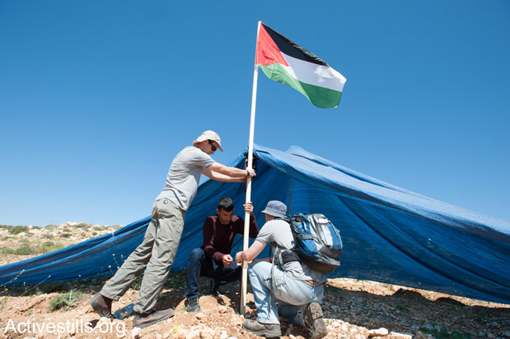 Palestinian and Israeli activists plant a Palestinian flag at a tent placed by settlers on land belonging to the West Bank village of Khirbet An-Nahla, April 18, 2014. All Israeli settlements on occupied Palestinian territory are illegal under international law. (Activestills.org)