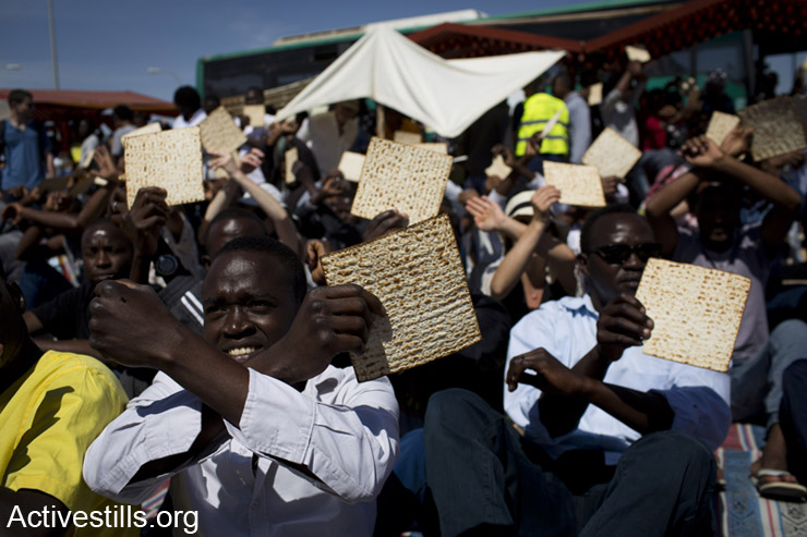 """African Asylum Seekers hold Matza during a Passover event outside the Holot detention center, April 11, 2014. Israeli activists and members of the African Asylum seekers community in Tel Aviv held an alternative Passover event outside the """"Holot"""" prison in the Negev desert in the South of Israel, to protest against the prison and to call Israel to recognize the Refugee tights of Asylum Seekers."""