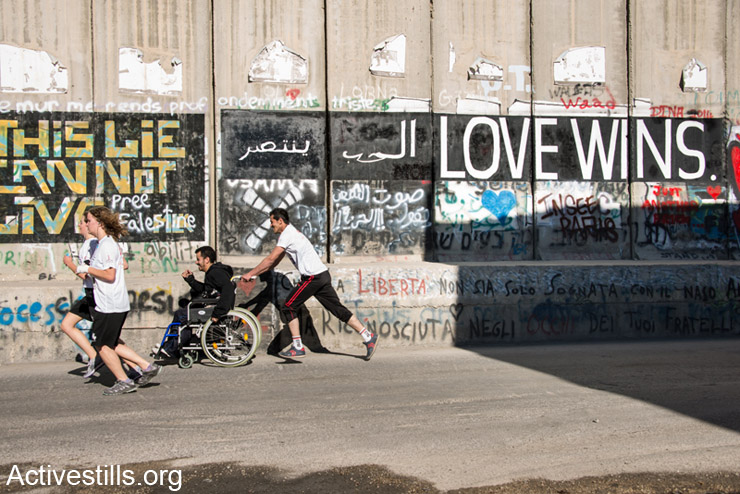 """A Palestinian runner pushes a friend in a wheelchair along the Israeli separation wall dividing the West Bank town of Bethlehem during the second annual Palestine Marathon, April 11, 2014. Some 2,500 Palestinian and 700 international runners participated in 5K, 10K, half marathon and full marathon races under the title """"Right to Movement"""". Full marathon runners had to complete two laps of the same route, as organizers were unable to find a single course of 42 uninterrupted kilometers under Palestinian Authority control."""