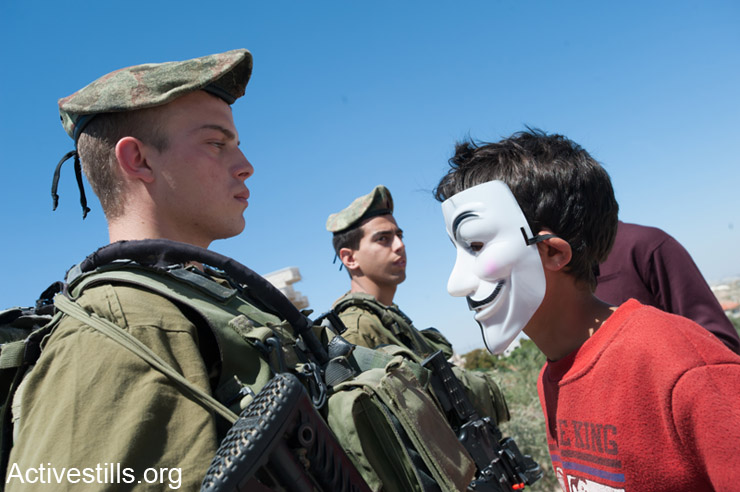 Masked Palestinian activists confront Israeli soldiers during the weekly demonstration against the Israeli separation barrier in the West Bank village of Al Ma'sara, April 11, 2014. The separation barrier would cut off the village from its agricultural lands if it is built as planned.