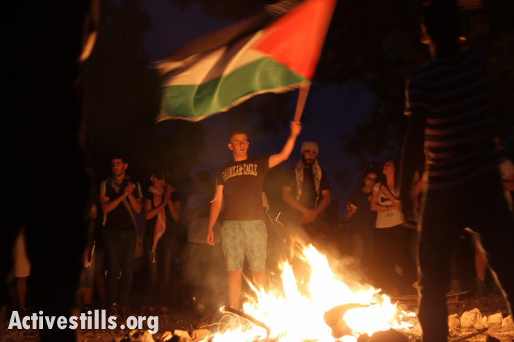 Palestinian citizens of Israel sing around a campfire the night before the March of Return to the village of Lubya in Israel's north.