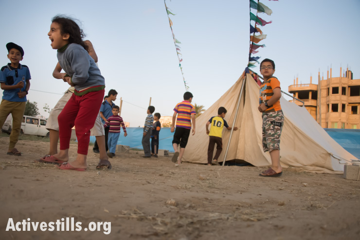 Children play near a tent set up for a Nakba commemoration event in Maghazi Refugee Camp, Gaza Strip, May 11, 2014. Some 75 percent of Gaza residents are refugees whose original homes were in what is now Israel.