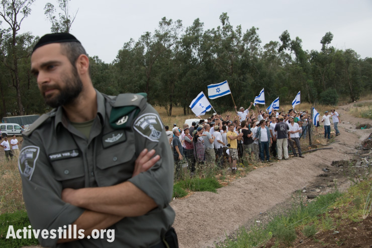 An Israeli policeman stands guard as Jewish Israelis wave flags and shout at those participating in the march (Activestills)