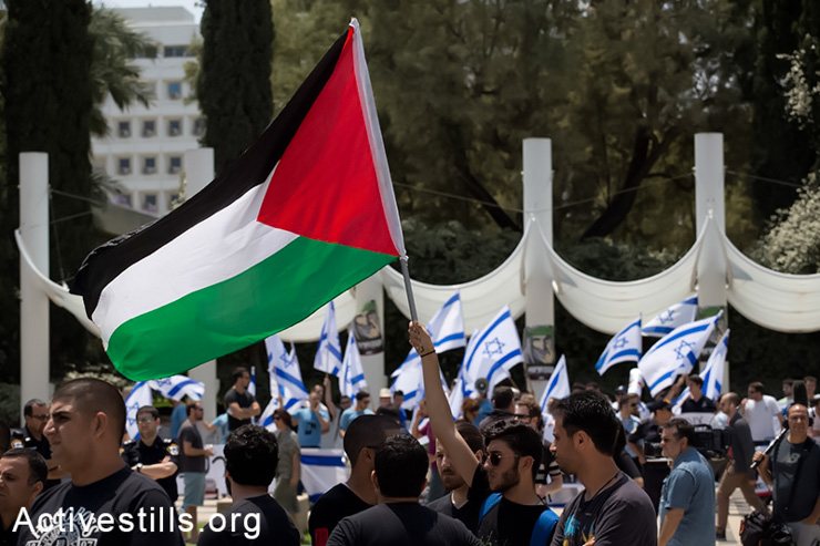 A student raises the Palestinian flag during a ceremony held by Palestinian students living in Israel and Israeli supporters commemorating the Nakba outside the Tel Aviv University, May 11, 2014. Right-wing nationalists from the group Im Tirzu, seen in the back, tried to interrupt the ceremony. (Activestills.org)
