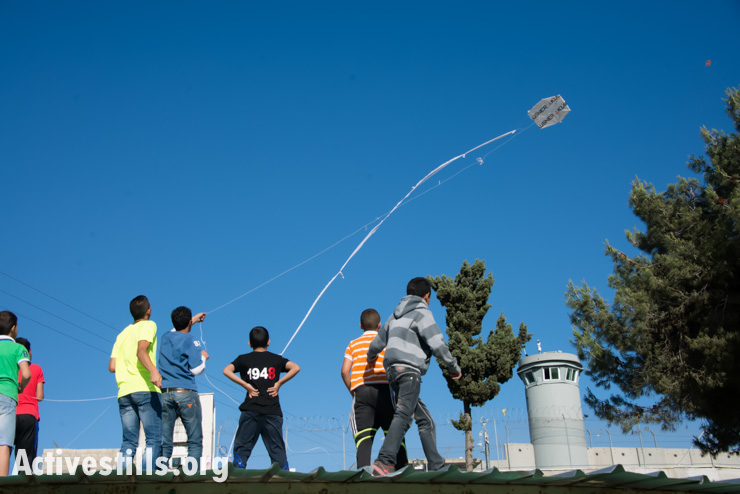 Children from Aida Refugee Camp fly kites over the Israeli separation wall during a Nakba commemoration event, May 14, 2014.
