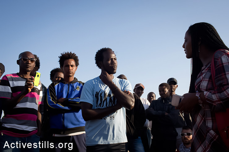Meron Estrfanos, an Eritrean journalist living in Sweden, speaks to African Asylum seekers jailed in the Holot detention center as they gather outside the facility in the Negev Desert, May 11, 2014. (Activestills.org)