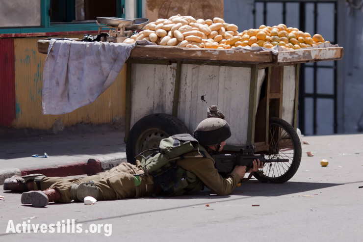 An Israeli soldier aims a rifle fitted for shooting rubber-coated steel bullets at Palestinians during clashes in the centre of Hebron at the 66th anniversary of Nakba, May 15, 2014.