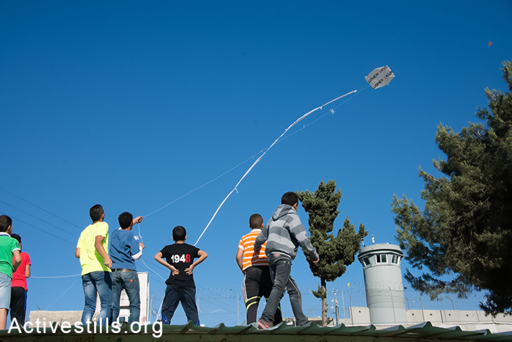"""Children from Aida Refugee Camp fly kites over the Israeli separation wall during a Nakba commemoration event, May 14, 2014. Nakba, Arabic for """"catastrophe,"""" is the term given to the forced displacement of some 750,000 Palestinian refugees from 500 communities by Zionist forces before, during and after the 1948 War. (Activestills.org)"""
