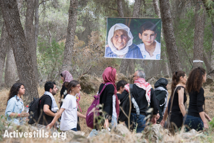 Palestinian citizens of Israel pass photos of Palestinian refugees during the march (Activestills)