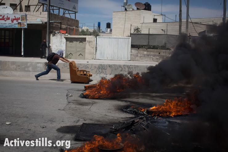 A Palestinian youth pushes a sofa toward burning barricades during Nakba Day clashes at Qalandiya checkpoint, West Bank, May 15, 2014. (Activestills.org)