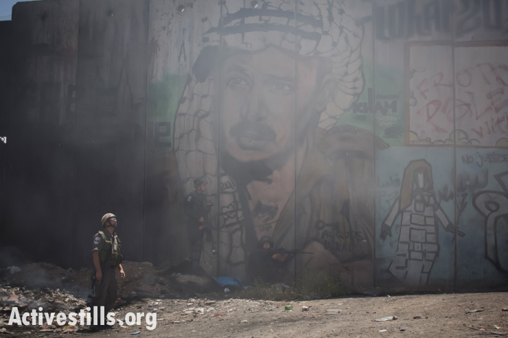 An Israeli border policeman stands near the Israeli separation wall during a protest commemorating the Nakba at Qalandiya checkpoint, West Bank, May 15, 2014.