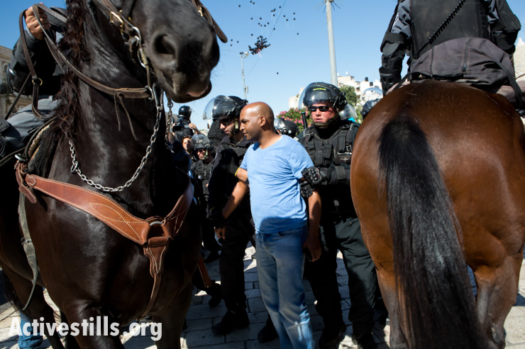 Israeli policemen detain a Palestinian man during a protest commemorating the Nakba at Damascus gate, outside Jerusalem's old city, May 15, 2014.