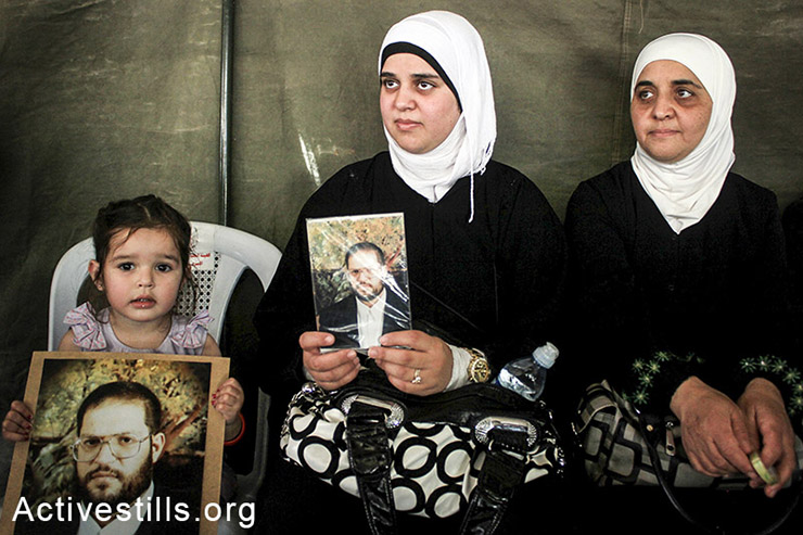 The family of Bahaa Yaish hold his picture in the protest tent in Nablus city, May 3rd, Yaish is a Palestinian administrative prisoner who spent 10 months in Israeli prisons. (Ahmad al-Bazz/Activestills.org)