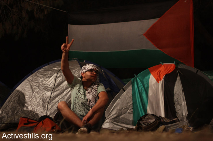 A Palestinian citizen of Israel sits near a tent in a camp a day before the march of return in the village of Lubya in northern Israel, May 5, 2014. (Activestills)