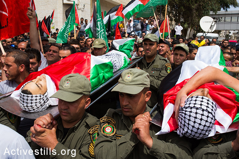 Members of the Palestinian national security forces carry the bodies of Nadim Seeam Abu Kara and Muhammad Abu Da'har during their funeral procession in the West Bank city of Ramallah on May 16, 2014. Abu Kara and Muhammad Abu Da'har were shot dead by Israeli forces during clashes the previous day outside the Israeli-run Ofer prison following a protest commemorating the Nakba. Foreign press published that the two died in a Ramallah hospital after being shot in the chest during a protest to demand the release of thousands of Palestinians held by Israel. (Activestills.org)
