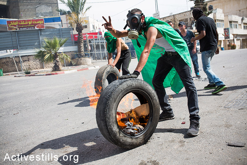 Palestinian youth seen during clashes with Israeli forces after the funeral of two Palestinians that were killed during Nakba Day clashes on May 16, 2014,  A'ram, West Bank. The two Palestinians were killed during Nakba day clashes with Israeli security forces at Betunia village.(Activestills.org)