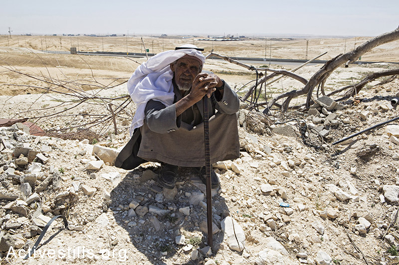 A man from the Zanoun family sits next to the ruins of his house a few hours after it was demolished in the unrecognized bedouin village of Wadi Al Na'am, Negev Desert, May 18, 2014. A women with her 5 children, the oldest of them is 5 years old, were living in the house demolished by the Israeli Land Administration. Wadi Al-am is the largest unrecognized village in Israel, with estimated 13,000 residents, most of them are internally displaced. The village is not connected to electricity. (Activestills.org)