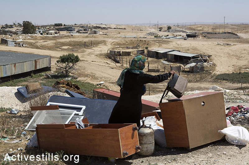 A woman from the Zanoun family is seen next to the ruins of her house a few hours after it was demolished in the unrecognized bedouin village of Wadi Al Na'am, Negev Desert, May 18, 2014. A women with her 5 children, the oldest of them is 5 years old, were living in the house demolished by the Israeli Land Administration. Wadi Al-am is the largest unrecognized village in Israel, with estimated 13,000 residents, most of them are internally displaced. The village is not connected to electricity. (Activestills.org)
