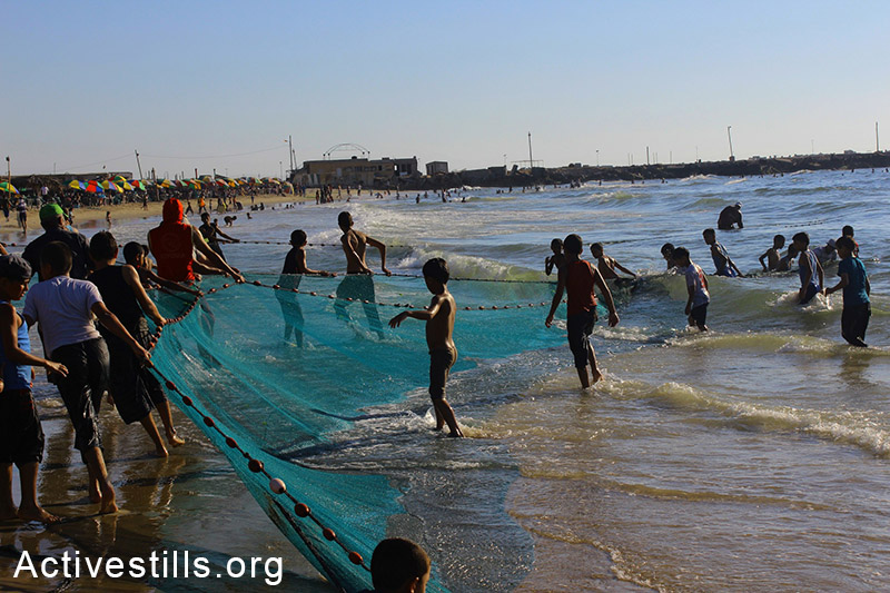 Children play near fishermen pulling out their nets at Gaza beach. (Basel Yazouri/Activestills.org)