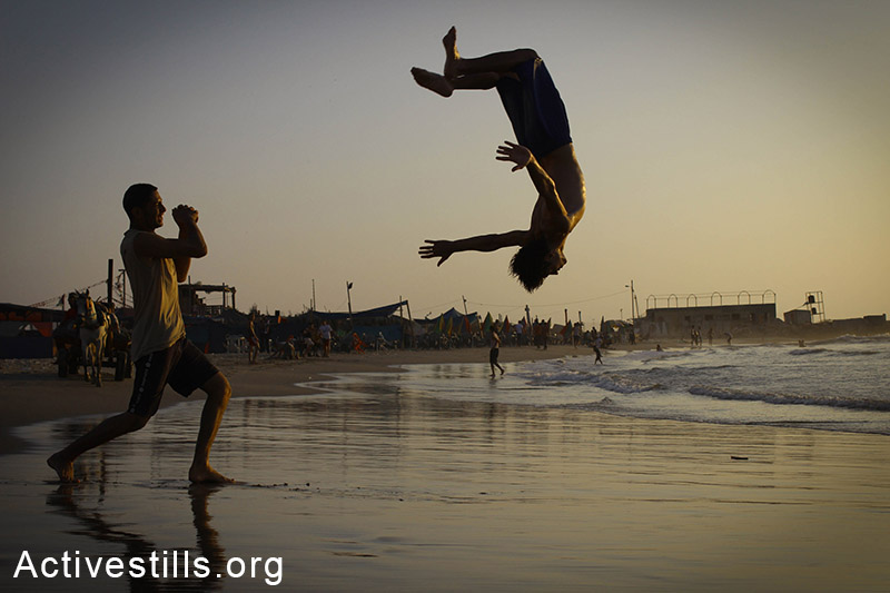 Two young men do acrobatic tricks on Gaza beach. (Basel Yazouri/Activestills.org)