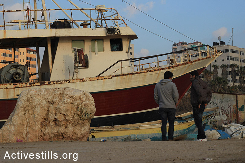 Young men stand beside an old ship in the Gaza port. (Basel Yazouri/Activestills.org)