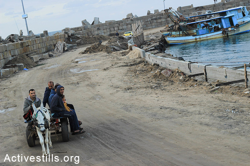A group of men pass by Gaza seaport on their wagon. (Basel Yazouri/Activestills.org