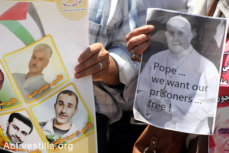 Palestinians hold the Pope picture calling him to take action on the Palestinian prisoners' issue, during a  demonstration in solidarity with hunger-striking Palestinian administrative prisoners, Nablus, West Bank, May 25, 2014. More than 100 Palestinian administrative prisoners in Israeli jails launched a mass, open-ended hunger strike on Thursday, April 24, 2014. A few of them are now hospitalized in Israeli medical centres due to the strike. (Ahmad al-Bazz/Activestills.org)