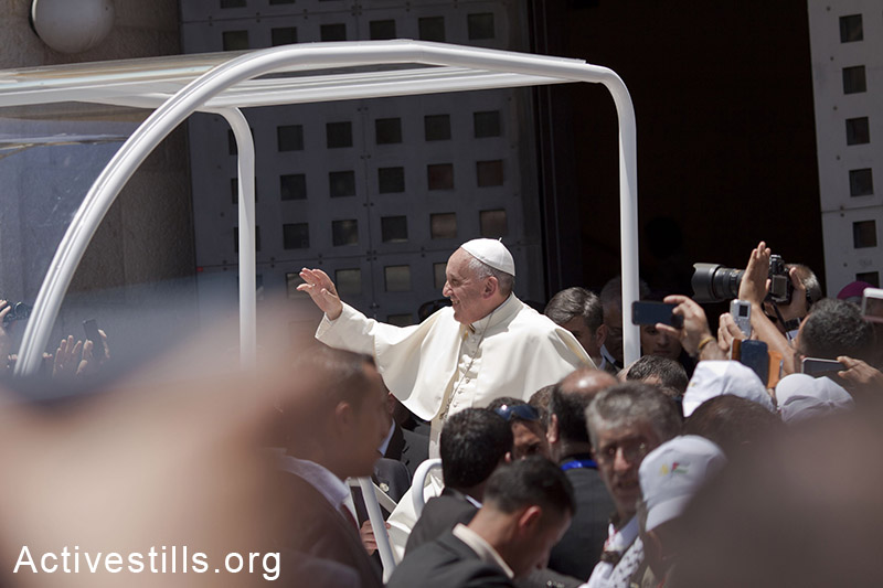 Pope Francis waves to the crowd, from his pope-mobile, as he leaves the Manger Square after presiding over an open-air mass on May 25, 2014, outside the Church of the Nativity in the West Bank  town of Bethlehem. (Mustafa Bader/Activestills.org)
